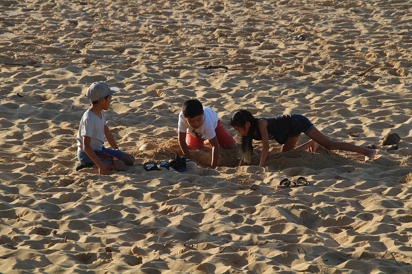 The kids from today's tour playing in the sand at Pipeline.
